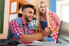 Dos estudiantes jovenes en la sala de clase de la universidad, alto ordenador portátil sonriente de la colegiala de la demostraci Foto de archivo libre de regalías