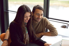 Dos estudiantes jovenes que estudian junto en biblioteca Imagenes de archivo