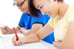 Dos estudiantes jovenes que estudian junto en sala de clase Imágenes de archivo libres de regalías