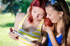 Dos estudiantes jovenes que se sientan en parque con PC de la tableta Imagen de archivo libre de regalías