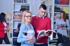 Dos estudiantes jovenes que trabajan junto en la biblioteca Fotografía de archivo