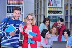 Dos estudiantes jovenes que trabajan junto en la biblioteca Fotografía de archivo libre de regalías