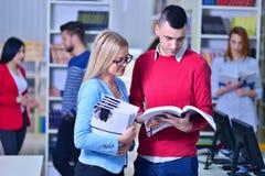 Dos estudiantes jovenes que trabajan junto en la biblioteca Imagen de archivo libre de regalías