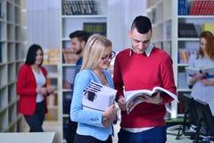 Dos estudiantes jovenes que trabajan junto en la biblioteca Fotos de archivo