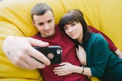 Dos estudiantes jovenes sonrientes hacen el selfie hermoso El retrato de la gente joven en un cuarto en una silla amarilla empaqu Fotos de archivo libres de regalías