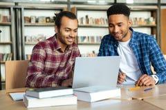Dos estudiantes masculinos multiculturales que estudian con el ordenador portátil Foto de archivo libre de regalías