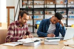 Dos estudiantes masculinos multiculturales que estudian con el ordenador portátil Imagen de archivo libre de regalías