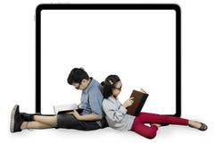 Dos estudiantes nerdy con los libros y whiteboard Foto de archivo libre de regalías