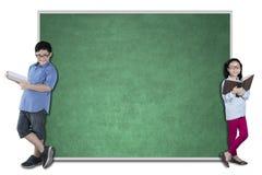 Dos estudiantes nerdy con una pizarra vacía Fotografía de archivo libre de regalías