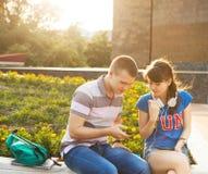 Dos estudiantes o adolescentes con el teléfono móvil al aire libre Foto de archivo libre de regalías