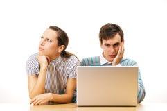 Dos estudiantes pensativos con la computadora portátil Foto de archivo libre de regalías