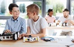 Dos estudiantes pre-adolescentes que socializan durante clase de la robótica Foto de archivo libre de regalías