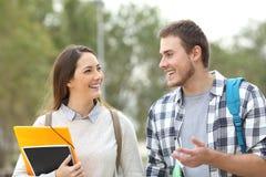 Dos estudiantes que caminan y que hablan imagen de archivo libre de regalías