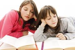 Dos estudiantes que estudian en el suelo Imagen de archivo libre de regalías
