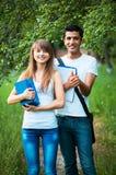 Dos estudiantes que estudian en parque con el libro al aire libre Imagenes de archivo