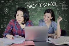 Dos estudiantes que hacen el schoolwork en la sala de clase Foto de archivo