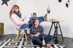 Dos estudiantes que hacen la preparación junta y que se ayudan que se sienta en una tabla en casa con un fondo hogareño Fotografía de archivo