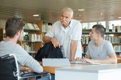 Dos estudiantes que leen en biblioteca con el profesor mayor Fotografía de archivo libre de regalías