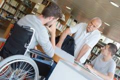 Dos estudiantes que leen en biblioteca con el profesor mayor Imagenes de archivo