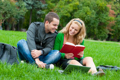 Dos estudiantes que leen un libro en la hierba Imagen de archivo libre de regalías
