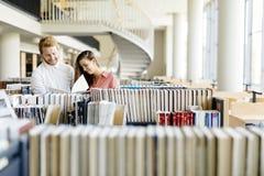 Dos estudiantes que leen y que estudian en biblioteca imagen de archivo libre de regalías