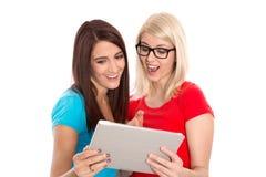 Dos estudiantes que se divierten con la tableta digital. Imagen de archivo