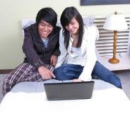 Dos estudiantes que se relajan en la cama con la computadora portátil Foto de archivo