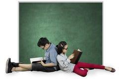 Dos estudiantes que se sientan cerca de una pizarra vacía Foto de archivo