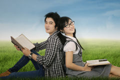 Dos estudiantes que se sientan en hierba Fotos de archivo libres de regalías