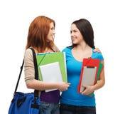 Dos estudiantes sonrientes con el bolso y las carpetas Fotografía de archivo libre de regalías