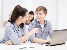 Dos estudiantes sonrientes con el ordenador portátil Foto de archivo