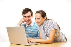Dos estudiantes sonrientes con la computadora portátil Fotografía de archivo libre de regalías