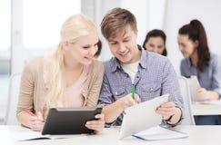 Dos estudiantes sonrientes con PC y los cuadernos de la tableta Imagen de archivo