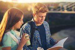 Dos estudiantes sonrientes con sus bolsos en estudiar de la escuela Fotos de archivo
