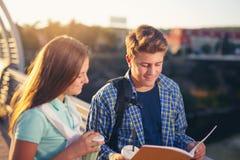Dos estudiantes sonrientes con sus bolsos en estudiar de la escuela Imagen de archivo libre de regalías