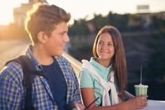 Dos estudiantes sonrientes con sus bolsos en estudiar de la escuela Foto de archivo