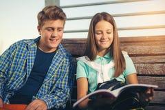 Dos estudiantes sonrientes con sus bolsos en estudiar de la escuela, al aire libre Imágenes de archivo libres de regalías