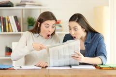 Dos estudiantes sorprendentes que leen un periódico Imágenes de archivo libres de regalías