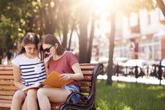 Dos estudiantes tienen mirada atenta en libro, se preparan para el examen final en la universidad, se sientan en banco en parque  Imagen de archivo