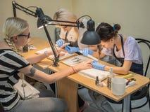 Dos estudiantes trabajan en una manicura de la escuela de entrenamiento del cliente de la manicura Rusia St Petersburg En julio d fotografía de archivo libre de regalías