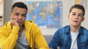 Dos estudiantes universitarios aburridos que miran la telenovela diurna de la TV y que comen las palomitas almacen de video