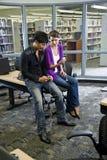 Dos estudiantes universitarios con los jugadores de música en biblioteca Fotos de archivo libres de regalías