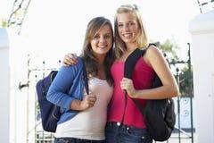 Dos estudiantes universitarios de sexo femenino que colocan la puerta exterior Fotos de archivo