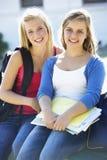 Dos estudiantes universitarios de sexo femenino que se sientan en banco con el libro de texto Imagenes de archivo