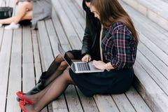 Dos estudiantes universitarios de sexo femenino que trabajan juntos en el red-libro portátil mientras que descansan después de co Imagen de archivo