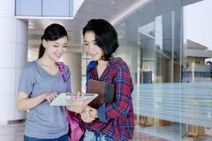Dos estudiantes universitarios de sexo femenino que usan la tableta junto Fotos de archivo