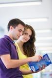 Dos estudiantes universitarios en biblioteca Imagen de archivo libre de regalías