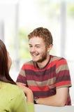Dos estudiantes universitarios jovenes que estudian junto en la sentada de la clase Imagen de archivo