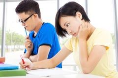 Dos estudiantes universitarios jovenes que sientan un examen Fotografía de archivo libre de regalías