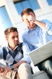 Dos estudiantes universitarios jovenes que usan la computadora portátil Imagen de archivo libre de regalías